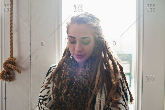 Young woman with long dreads in sunlight