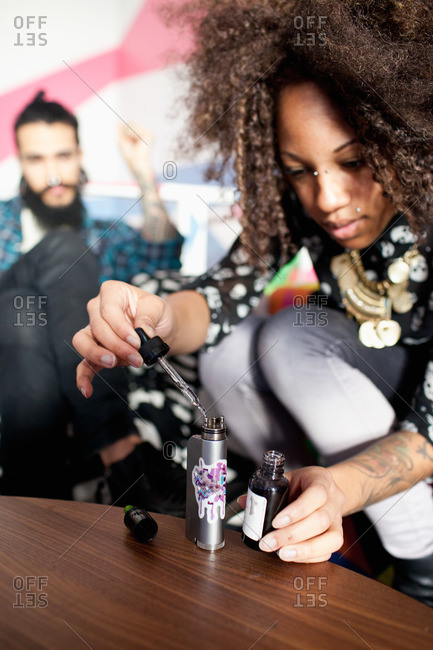 Young woman refilling vaporizer