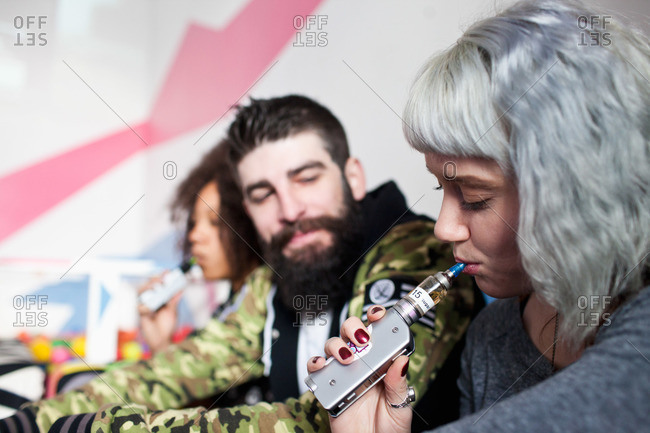 Young friends smoking with vaporizers together