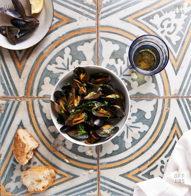 Bowl of mussels with herbs, crusty bread and beer