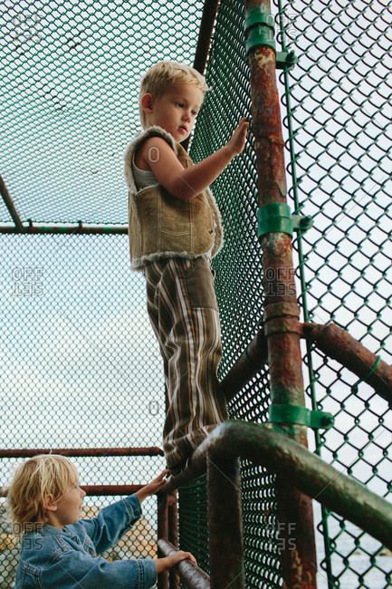 Boys climbing on a chain link fence overlooking the ocean