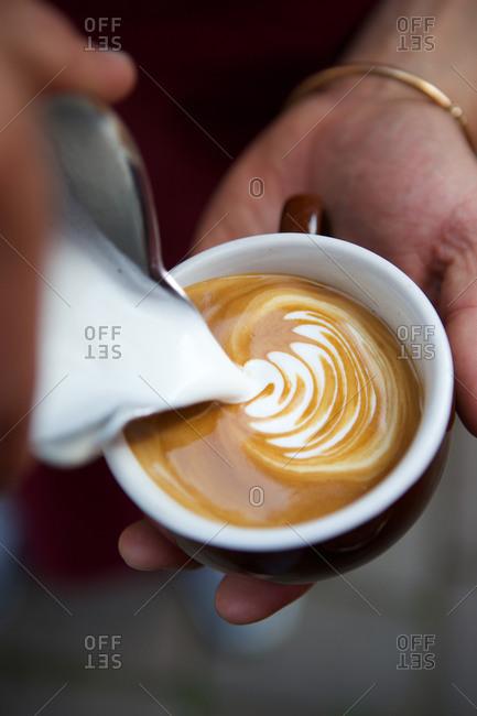 A barista pours milk into a latte