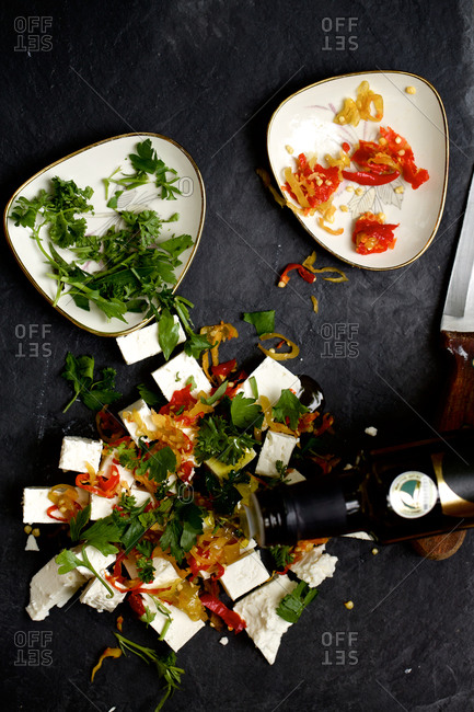 Olive oil pouring over feta cheese and vegetables
