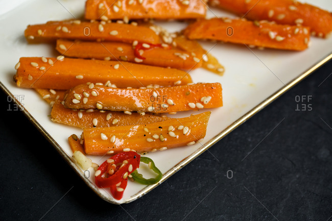 Carrot slices covered in oil and sesame seeds
