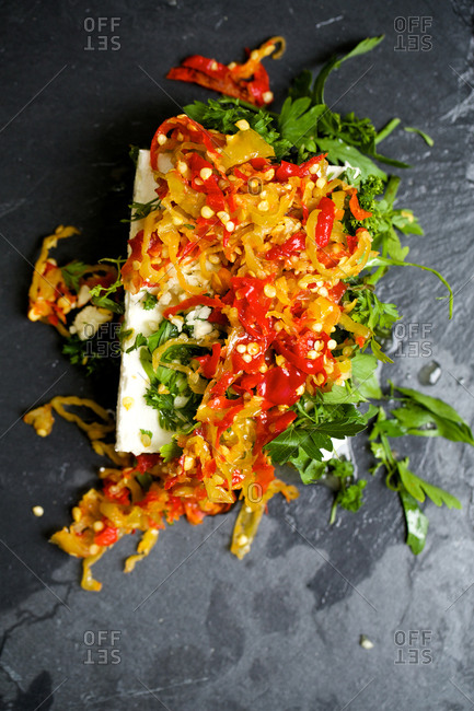 A rectangle of feta cheese topped with sliced peppers and chopped herbs