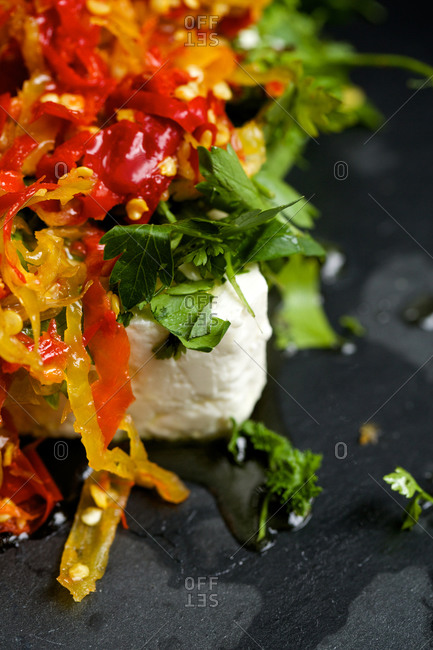 A rectangle of feta topped with sliced peppers and chopped herbs