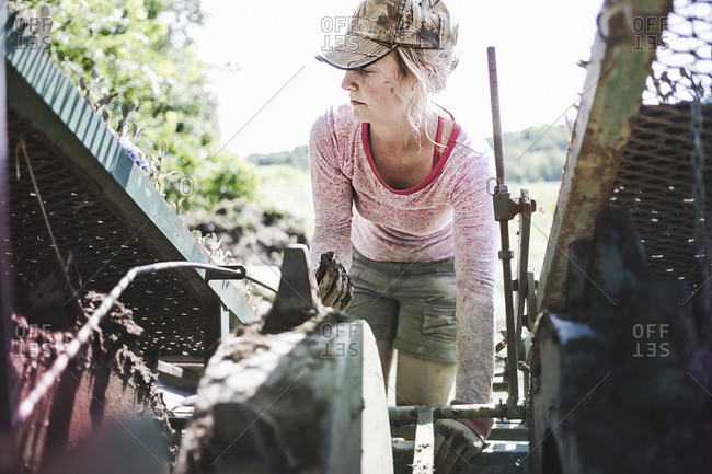 A woman works on farm machinery