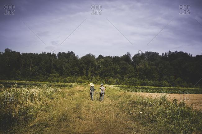 Two farmhands walk through a field