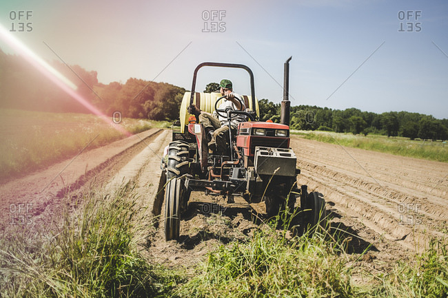 A farmhand on a tractor turns to check his work
