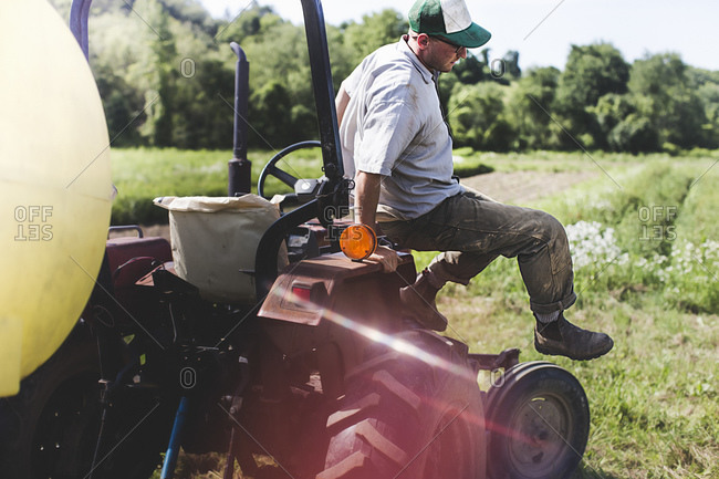 A farmhand hops off the front of a tractor