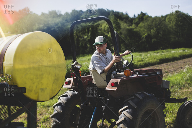 A farmhand drives a tractor and turns to check his work