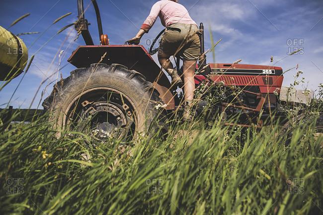 A farmhand climbs onto a tractor