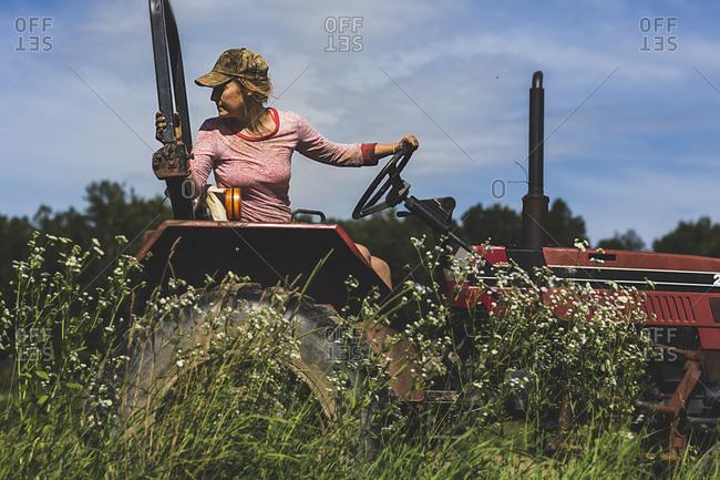 A farmhand drives a tractor across a field