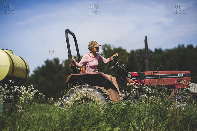 A farmhand drives a tractor carrying a yellow barrel across a field