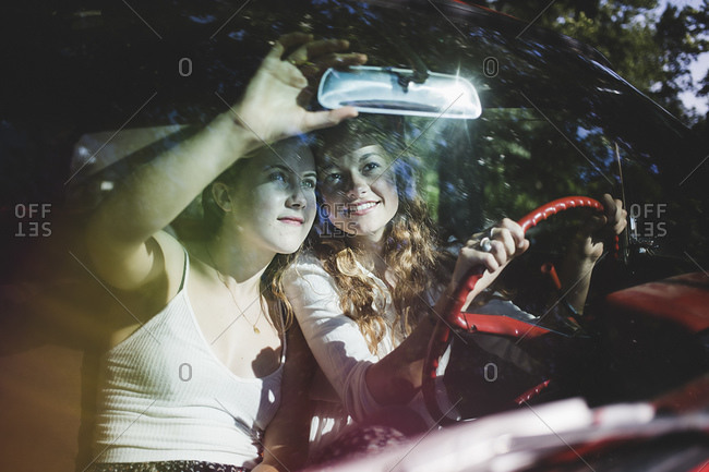 Two women look at themselves in a rear view mirror of a car