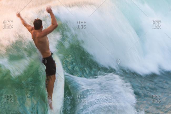 Surfer does a back flip off a wave