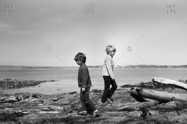 Boys walking on a rocky beach