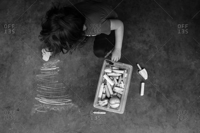 Boy drawing on cement with sidewalk chalk
