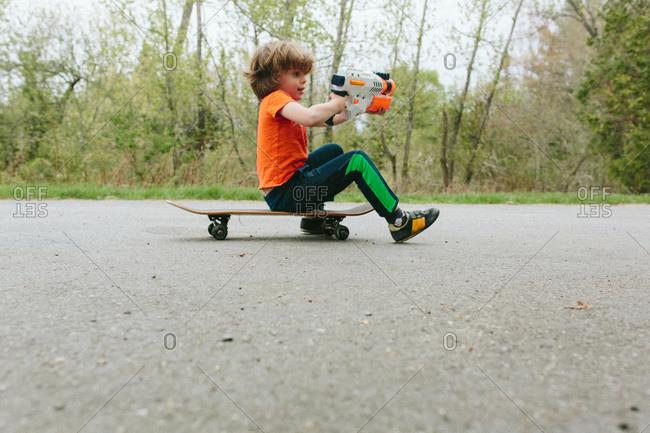 Boy sitting on a skateboard playing with a toy gun