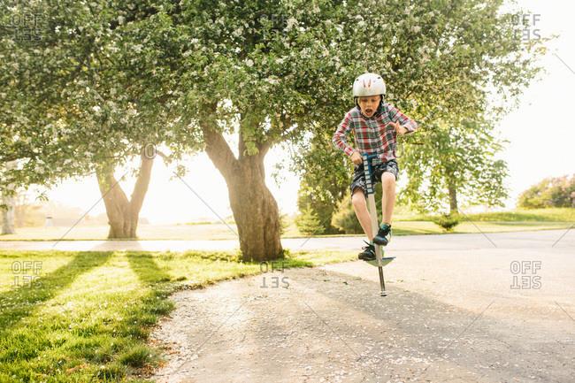 Boy bouncing on a pogo stick