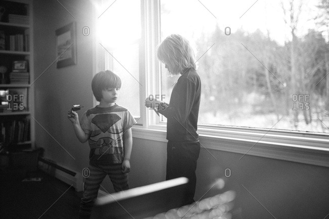 Boys standing in front of a window playing with paper airplanes