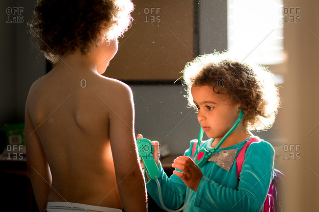 Girl playing doctor with her brother