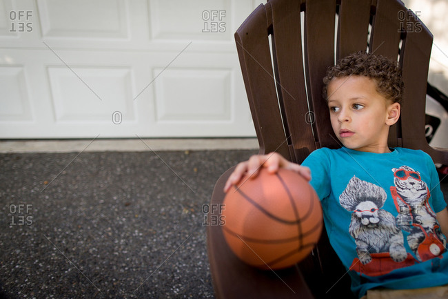 Boy staring in a lawn chair with a basketball