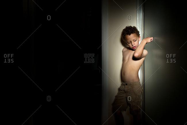 Boy in focused lighting looking at elbow