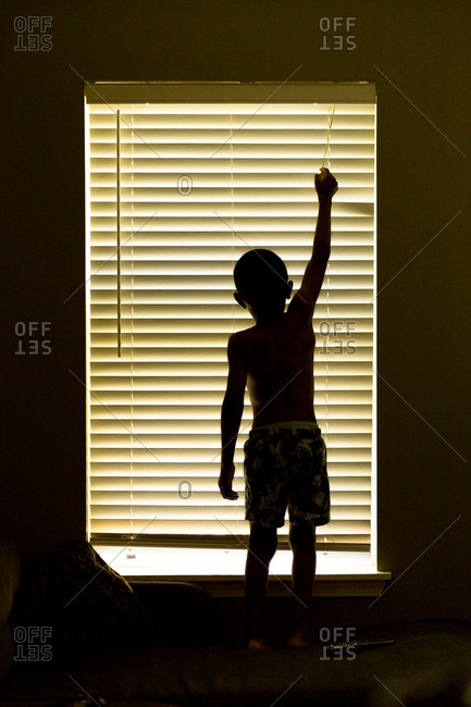 Boy standing on couch to adjust blinds