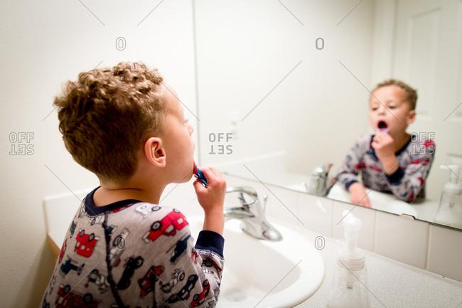Little boy in pajamas brushing teeth in bathroom