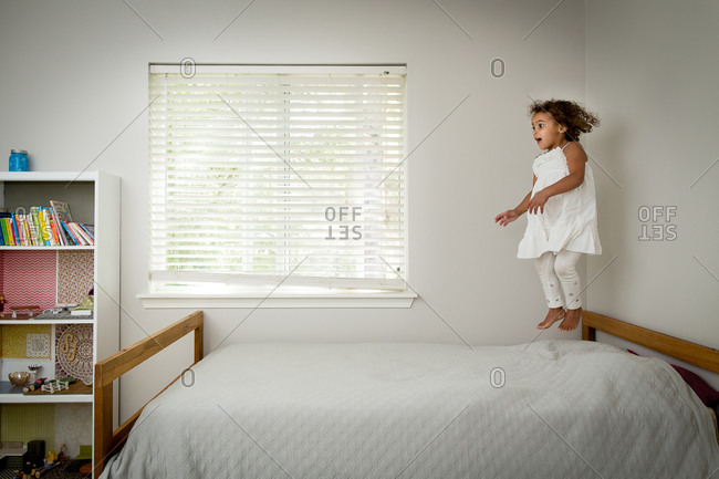 Girl in midair jumping on a bed