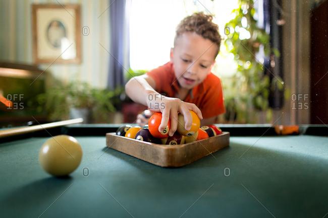 Boy racking pool balls on pool table