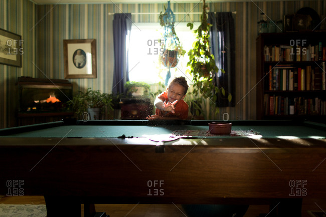 Little boy reaching into sunlight over pool table