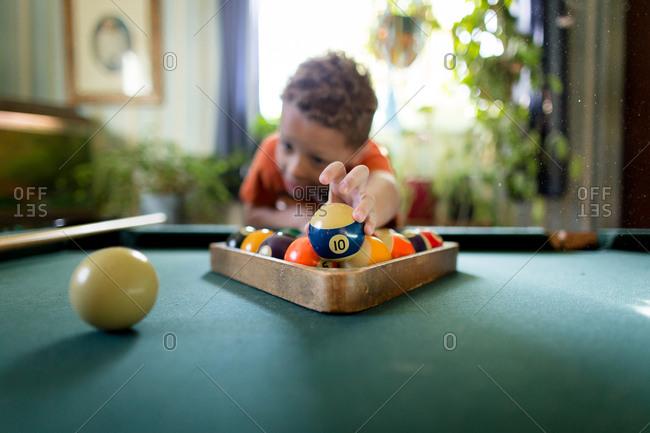 Boy racking balls on pool table