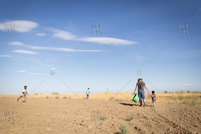 Farmer and kids walking in rural field