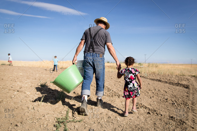 Farmer walking with little girl in rural field