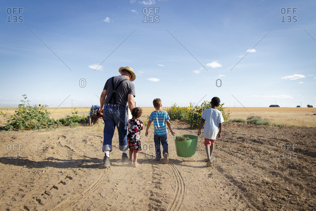 Farmer and kids walking in field with bucket