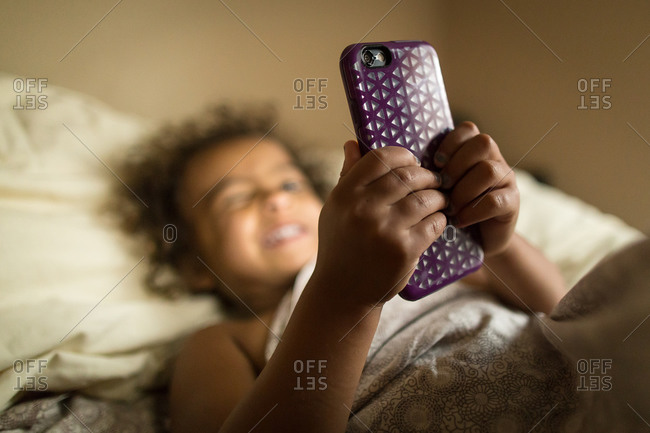 Smiling little girl under covers looking at phone
