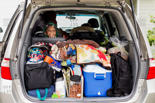 Boy looking out back of packed vehicle trunk