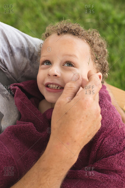 Little boy in blanket held in grandfather's arms