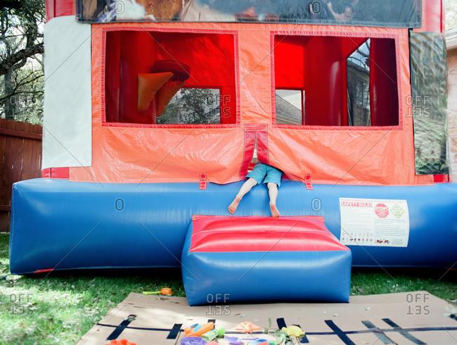 Feet of a little boy climbing into a bouncy house