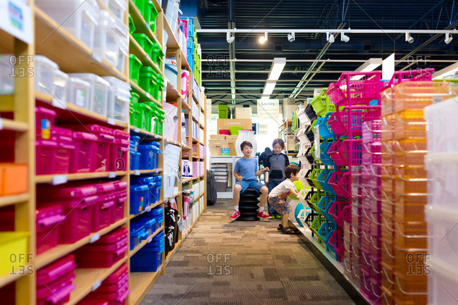 Three boys in a store full of containers
