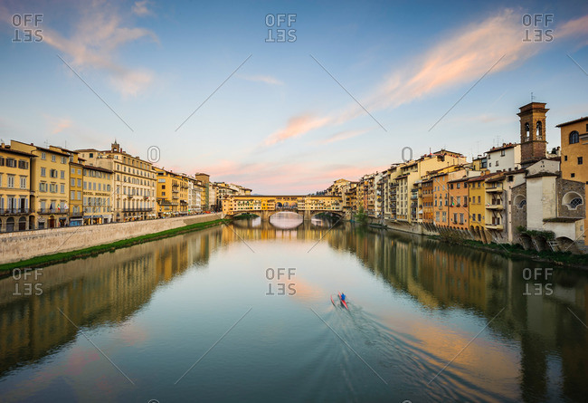 Rower on the Arno River with the Ponte Vecchio Bridge at dusk in Florence