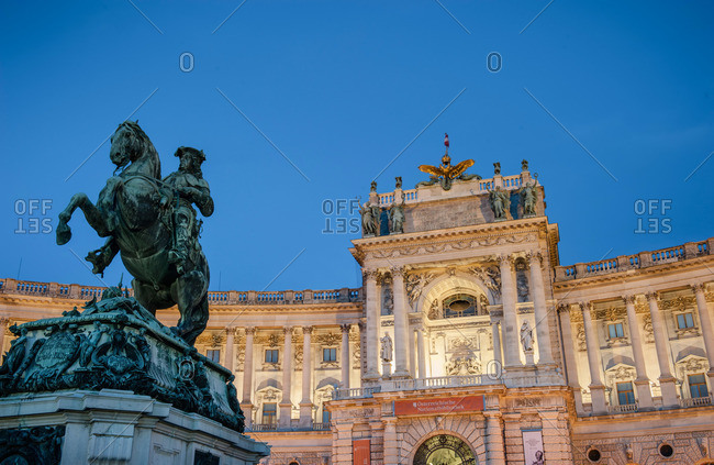 Vienna, Austria - June 9, 2012: The National Library at dusk in Vienna, with the statue of Prince Savoy