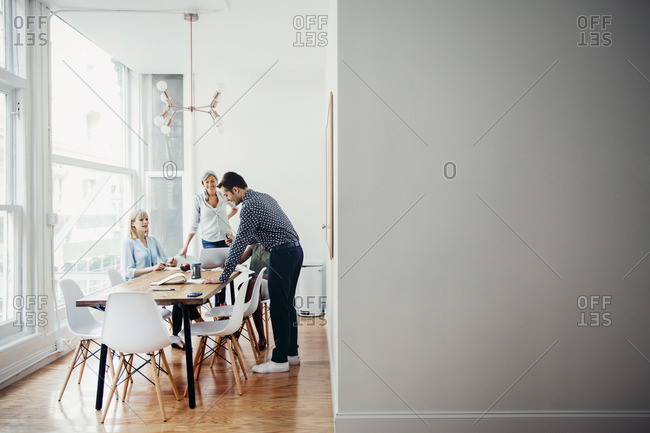 Four people meeting around a conference table