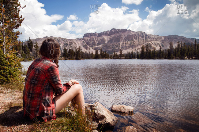Woman sitting by a lakeshore looking at mountains