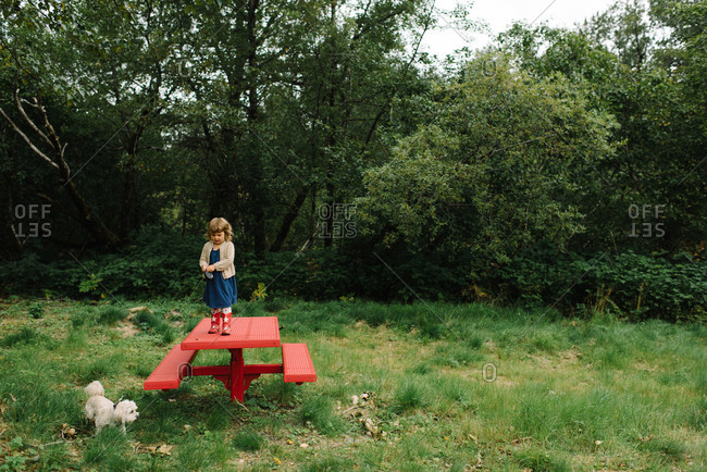 Little girl standing on a picnic table holding her dog's leash