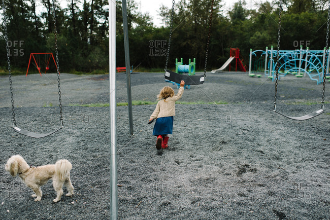 Little girl holding her dog's leash and pushing a swing in a playground