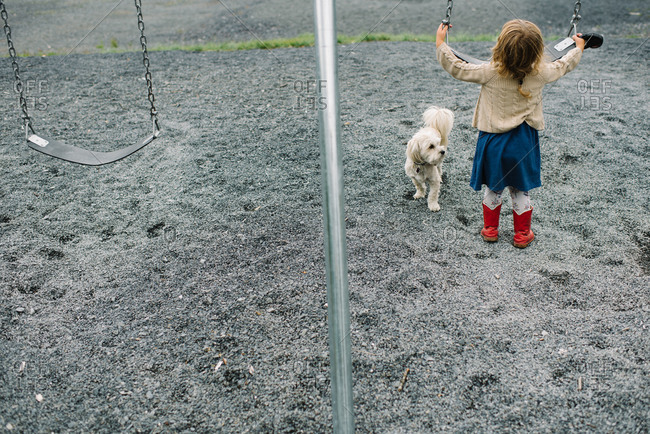 Little girl at a playground swing with her dog
