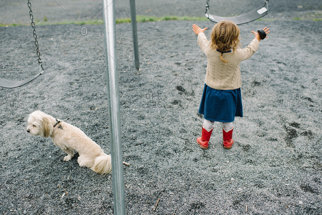 Little girl on a playground with her dog pushing a swing